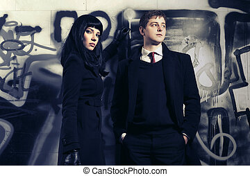 Young fashion couple standing next to graffiti wall