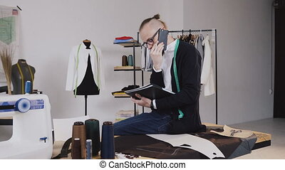 Young fashion designer or tailor sitting on table in atelier and talking phone and makes notes in his notebook. Young bearded man in glasses dressed in white shirt and black blouse with measure tape on neck working in atelier and talking phone