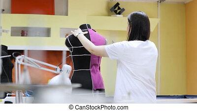 Young fashion designer, tailor and dressmaker adjusting...