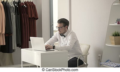 Young Fashion Designer Typing On Laptop at Workplace