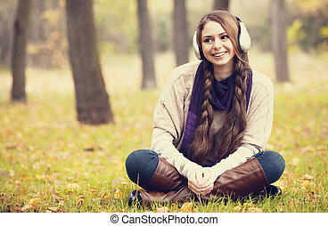 Young fashion girl with headphones at autumn park.