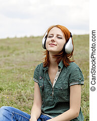 Young fashion girl with headphones at grass in spring time.