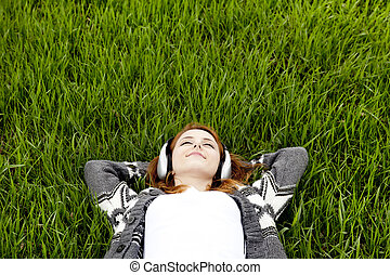 Young fashion girl with headphones lying at green spring...