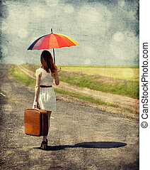 Young fashion girl with umbrella and suitcase at spring outdoor. Photo with retro bokeh at background.