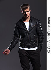 young fashion male model in leather jacket posing
