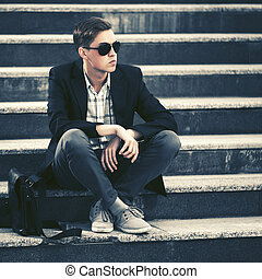 Young fashion man in sunglasses sitting on the steps
