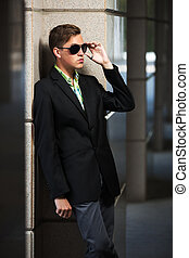 Young fashion man in sunglasses standing at the wall