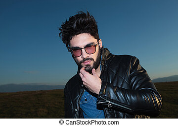 young fashion man scratching his beard and looking at the...