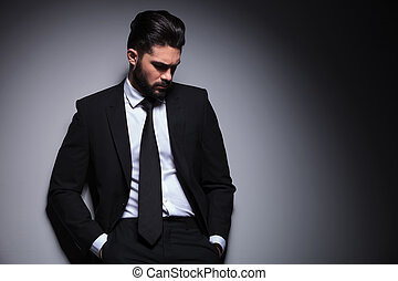 young fashion man with hands in pockets looks down - front...
