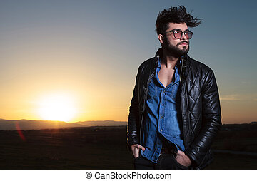 young fashion man with long beard standing with hands inpockets in the dusk
