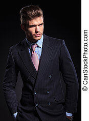 young fashion model in suit and tie looking away
