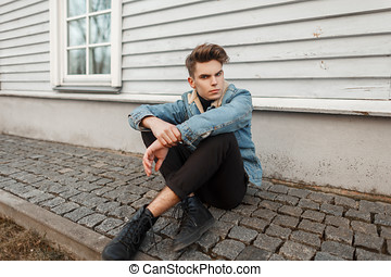 Young fashion model man in stylish jeans and black sneakers sits near a wooden wall