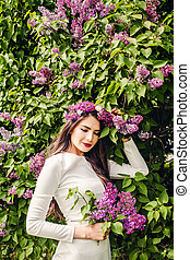 Young fashion model with lilac flowers in her hand in park outdoor. Beautiful woman portrait