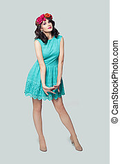 Young fashion model woman in blue dress standing on white background