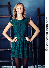 Young fashion model woman in green dress. Cute girl on blue rustik background