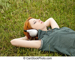 Young fashion with headphones lying at green grass in spring time.