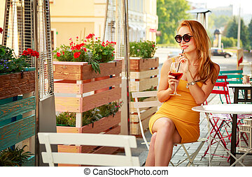 Young Fashion Woman Drinking Cocktail in a Cafe