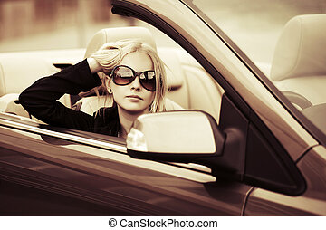 Young fashion woman in a convertible car
