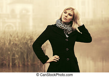 Young fashion woman in black coat walking outdoor
