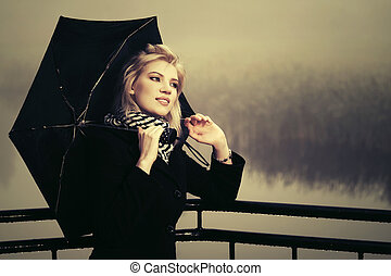 Young fashion woman in black coat with umbrella outdoor