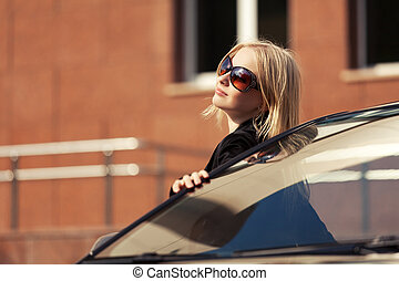 Young fashion woman in sunglasses standing by her car