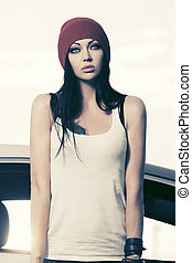 Young fashion woman in t-shirt standing next to her car