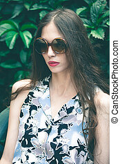young fashion woman portrait with sunglasses in garden