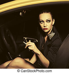 Young fashion woman smoking cigarette in a car
