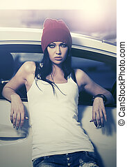 Young fashion woman standing next to her car