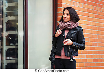 Young fashion woman wearing black leather jacket looking at window display