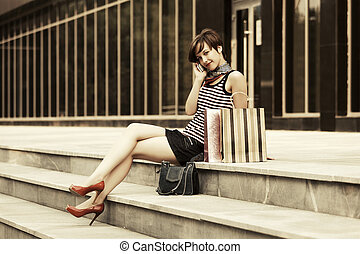 Young fashion woman with shopping bags calling on the phone