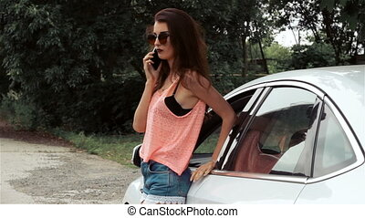young fashionable girl standing near a car and talking on the phone