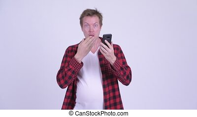 Young fat hipster man with big belly using phone and looking...