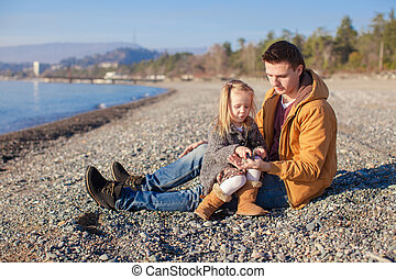 Young father and his little daughter at the beach on a sunny winter day