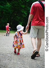 Young father and his little daughter walking