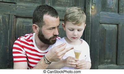 Young father and his little son eating ice cream. Sunny day....