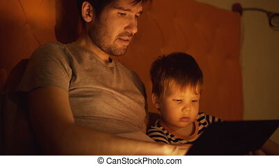 Young father and his little son watching cartoon movie using tablet computer while lying in bed in evening at home