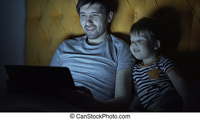 Young father and his little son watching cartoon movie using...