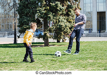 Young father and his son playing football in a park