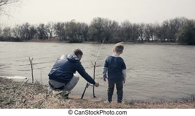 Young father and little son fishing with tackle together in...