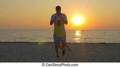 Young father and little son having fun on the beach