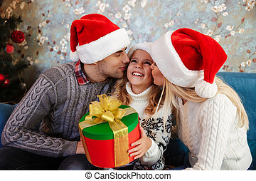 Young father and mother in Santa's hat kissing those little daughter while sitting on blue sofa at Chrismas morning