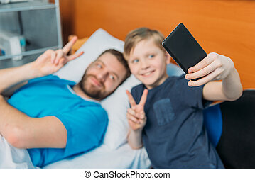 young father and son taking selfie on smartphone at ward, hospital patient care