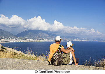 Young father and son with backpacks are sitting on the beach against the backdrop of the sea. Family travel concept