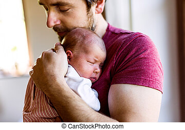 Young father at home holding his newborn baby girl. - Young...