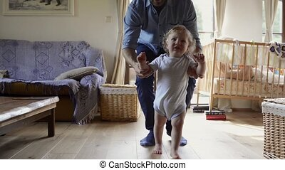 Young father at home with his little son doing first steps.