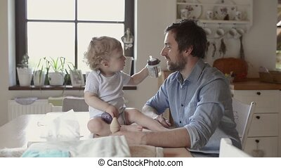 Young father at home with his little son playing together.