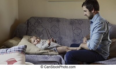 Young father at home with his little son changing his clothes.