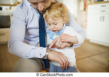 Young father at home with his son.