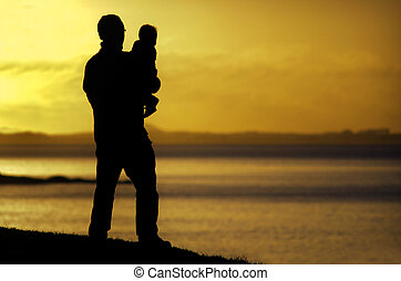 Silhouette of a young father carries his child on the beach during sunset.